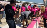 Johnson helps paint the wall pink to support breast cancer awareness
